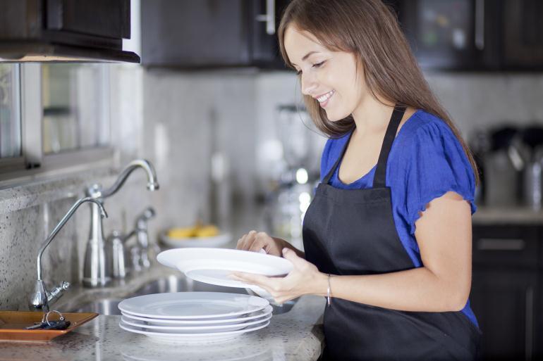 Девушка моет посуду